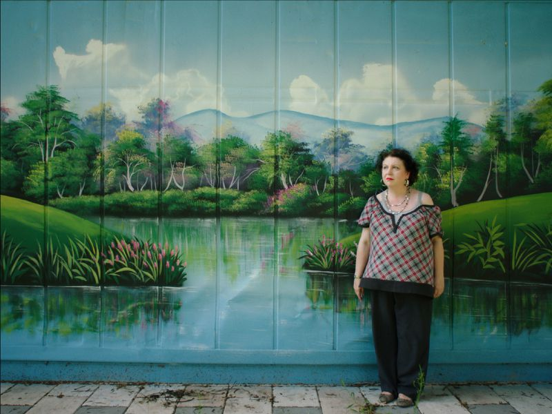 A woman stands in front of a giant painted mural depicting a lush green scene.