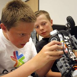 Cade Fuhriman, left, and teammate Jesse Jordan work on their robot as they take part in the Graphics & Robotic Exploration with Amazing Technology summer camp Friday, July 22, 2011, at the Warnock Engineering Building at the University of Utah.