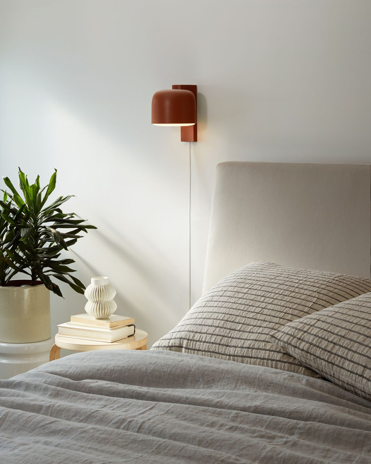 Red sconce next to bed.