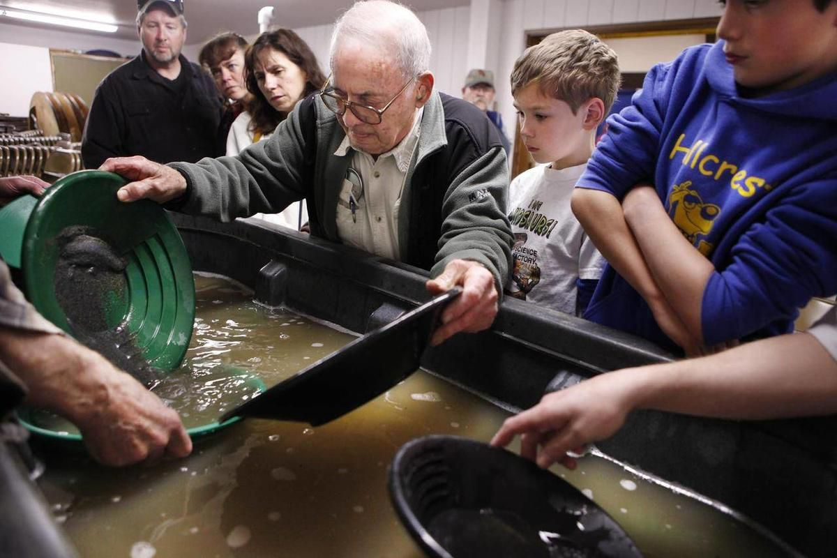 In this April 7, 2012 photo, Bill Peabody shows novices how to separate gold from black sand suing water and a gold pan during the gold prospectors show in North Bend, Ore.  Peabody has been prospecting as a hobby for 30 years. He started combing the grou