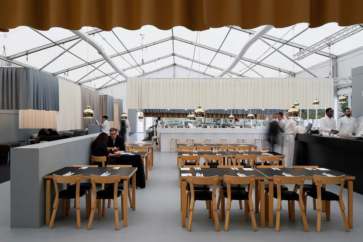 A dining room installed at Frieze's London art fair, with tables on a black floor with a white bar