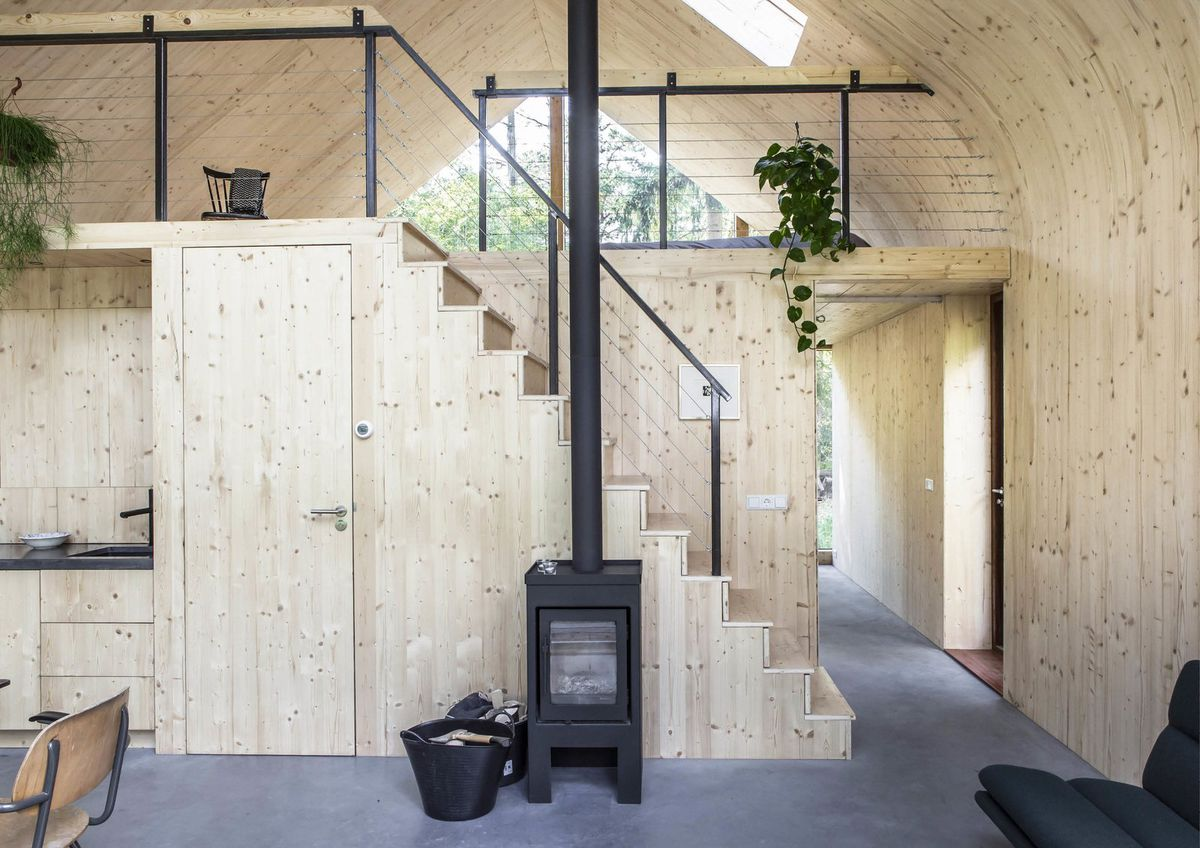 All-timber interior with staircase leading to a loft.