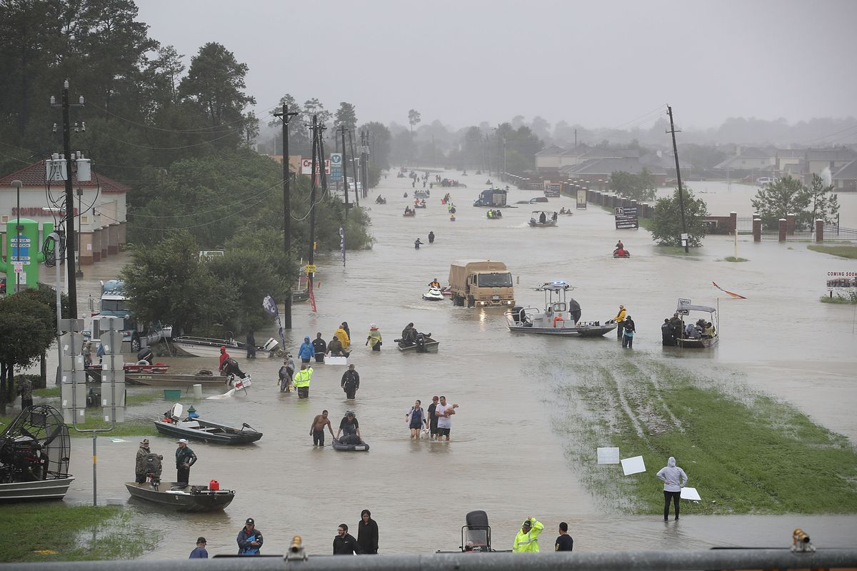 People walk down a flooded street in Houston during Hurricane Harvey
