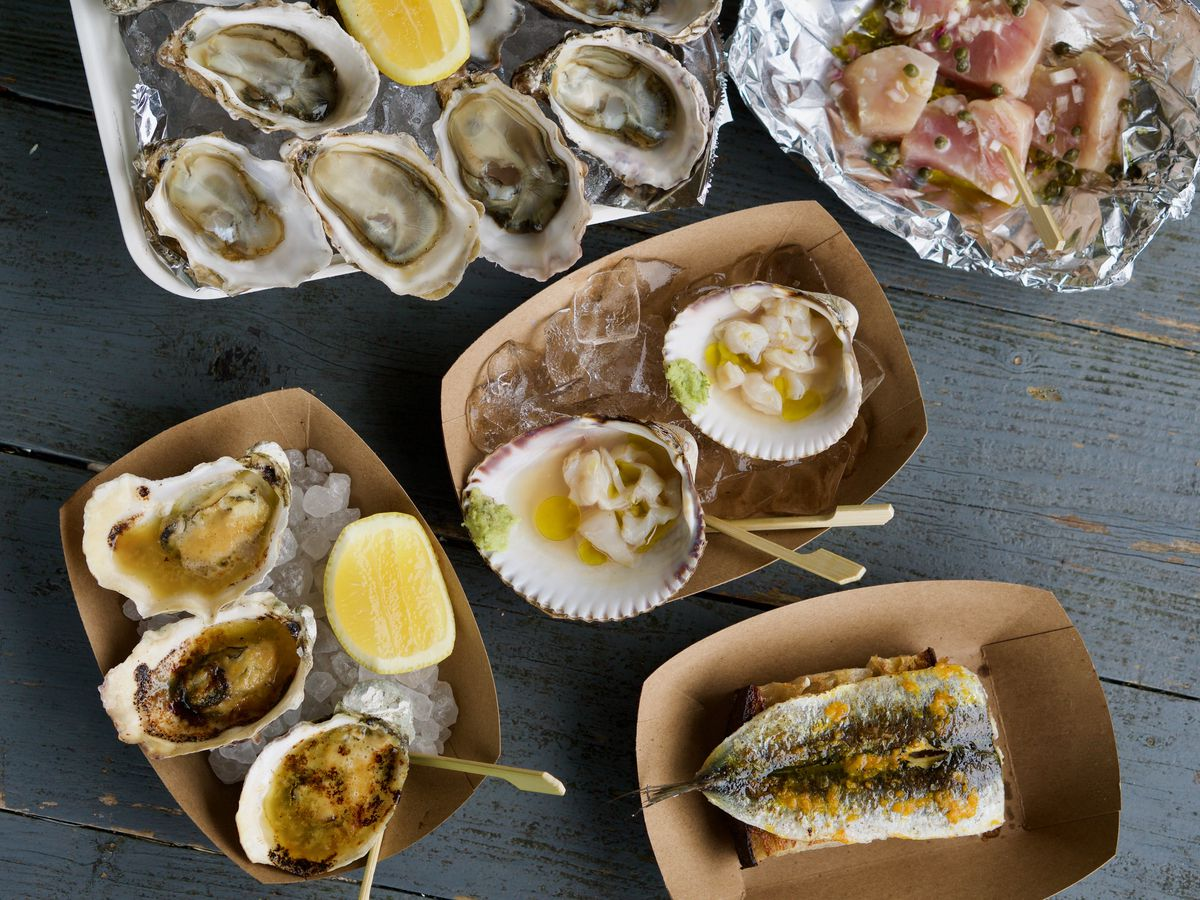 A spread of raw oysters on the half shell, albacore crudo, raw clams, sardine toast, and BBQ oysters with miso butter.