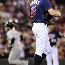Minnesota Twins pitcher Liam Hendriks looks away after giving up a two-run home run to New York Yankees' Nick Swisher, left, in the first inning of a baseball game, Monday, Sept. 24, 2012, in Minneapolis.
