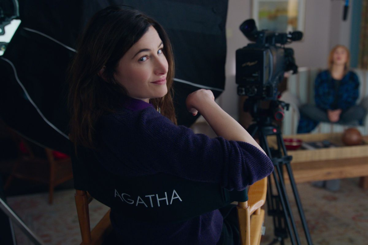 Agatha Harkness smirks over her shoulder as she sits in a director's chair in WandaVision, probably celebrating that she didn't get killed off like most MCU villains