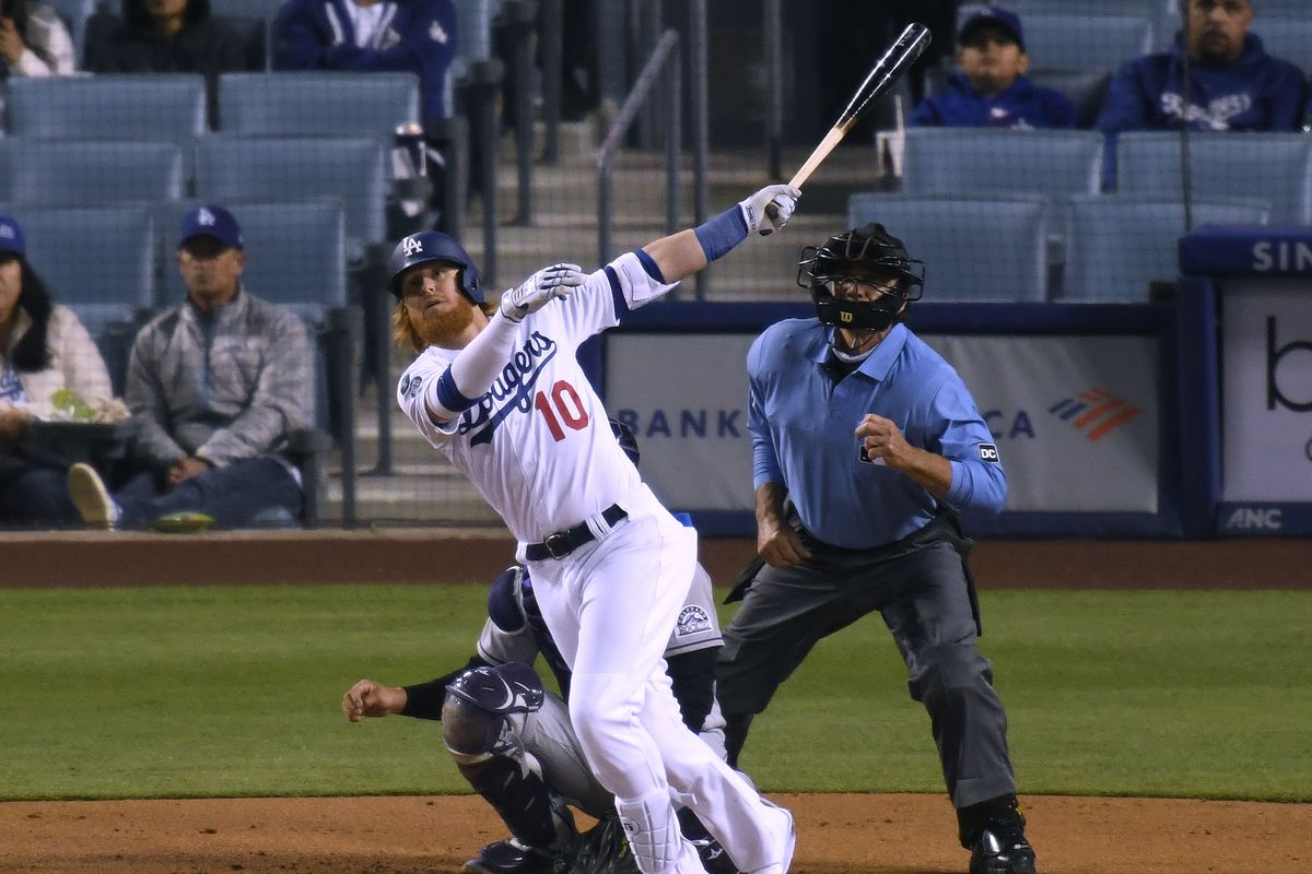 Justin Turner #10 of the Los Angeles Dodgers hits a solo homerun in front of Dom Nunez #3 of the Colorado Rockies and umpire Phil Cuzzi #10, to take a 3-0 lead, during the third inning at Dodger Stadium on April 14, 2021 in Los Angeles, California.