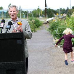Lily Munson, 4, skips away after interrupting Salt Lake City Mayor Ralph Becker's speech to give him flowers during the dedication of the Popperton Plots community garden in Salt Lake City on Friday, Aug. 22, 2014.