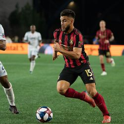 FOXBOROUGH, MA - APRIL 13: Atlanta United FC forward Hector Villalba #15 dribbles by New England Revolution defender Andrew Farrell #2 during the first half at Gillette Stadium on April 13, 2019 in Foxborough, Massachusetts. (Photo by J. Alexander Dolan - The Bent Musket)