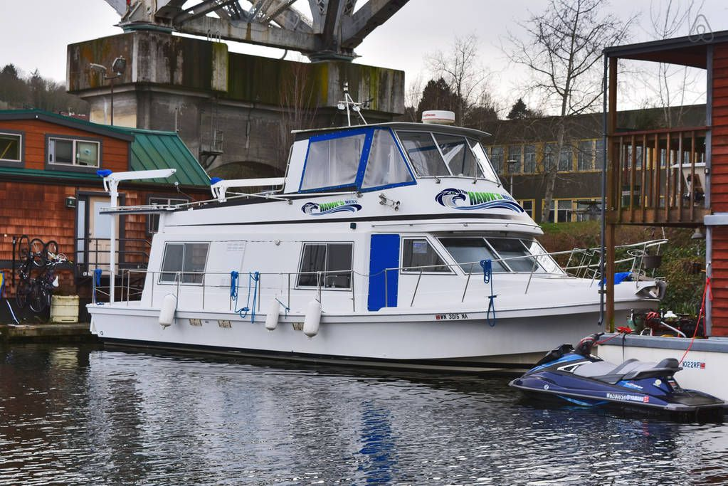 A white boat with a large cabin below and Seahawks-themed details