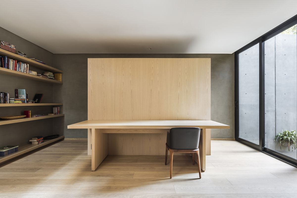 Study with light wood table and a glass wall to the right.