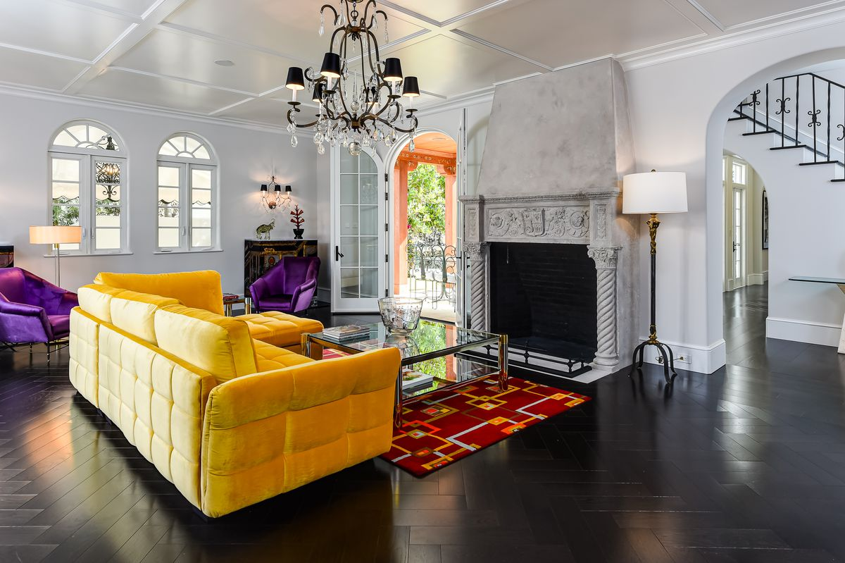 A living room features a concrete fireplace, bright yellow couch, purple chairs, and a red rug under a chandelier.