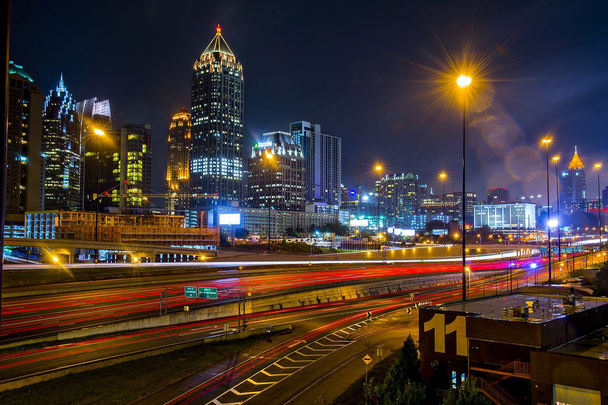 A skyline view of Atlanta at night with cars zipping by.