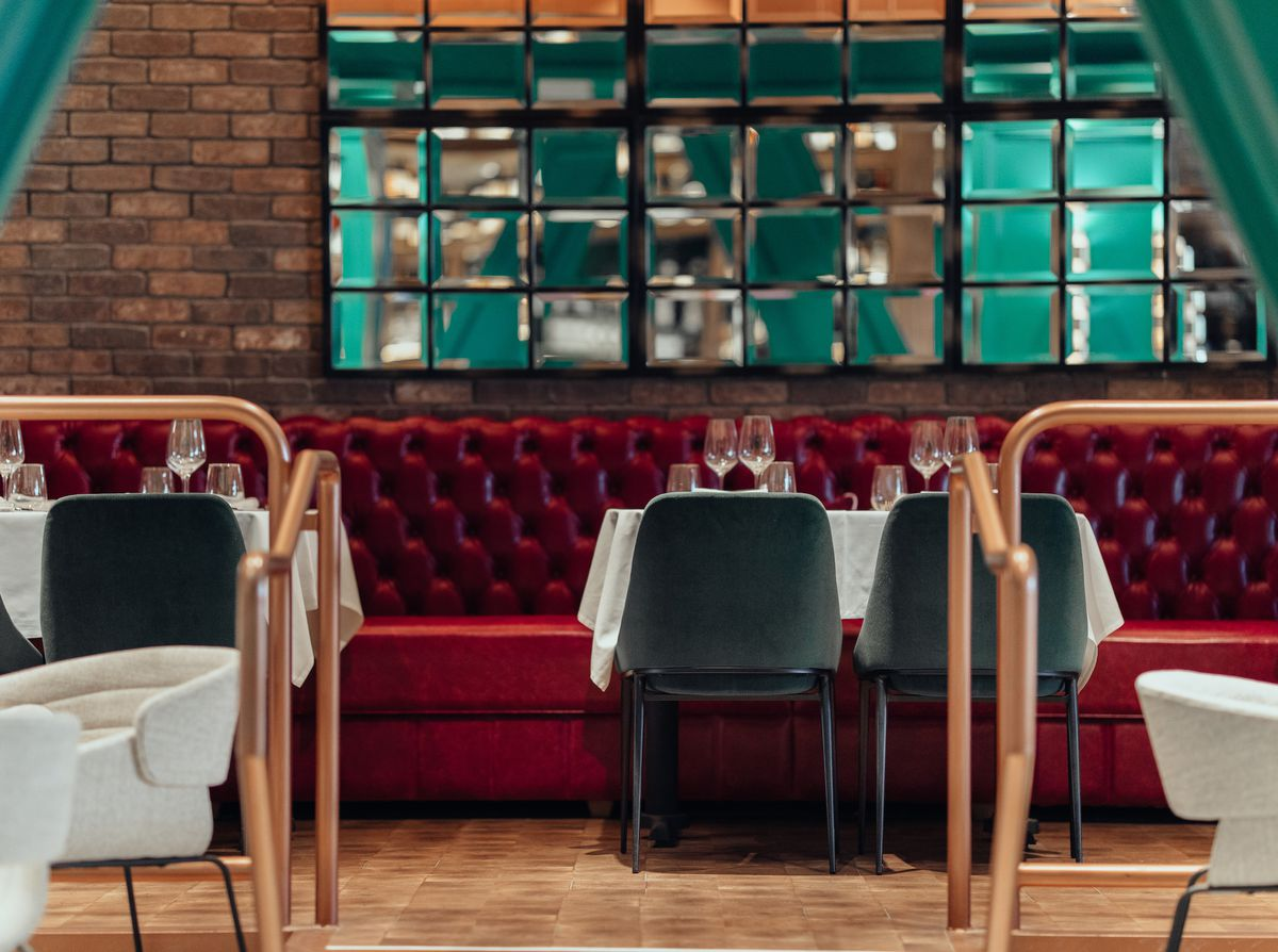A low-level view of a new restaurant with copper railings and white tablecloths and bright red seats.
