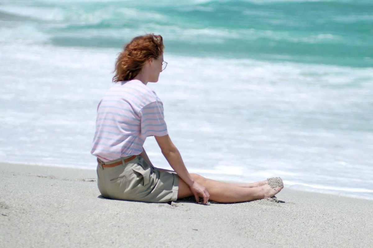 Still from 'Black Mirror' of a woman sitting on the beach