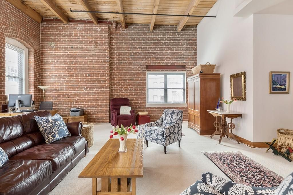 The end of the living room, with a brick wall and a single window as well as furniture.