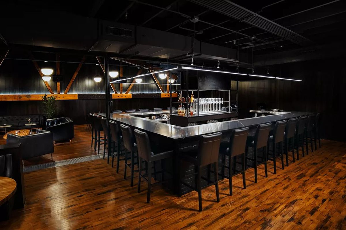 The dimly-lit bar space features a 22-seat Nero Marquina black marble bar.