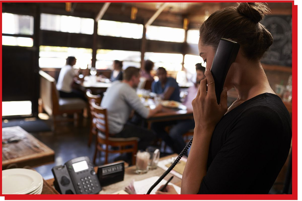Woman at a restaurant hostess stand on the phone.