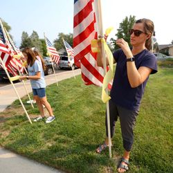 Lena McIllece, friend and neighbor, put up flags around the house belonging to the father of U.S. Marine Staff Sgt. Darin Taylor Hoover Jr. in Sandy on Friday, Aug. 27, 2021. Hoover Jr. was killed in the suicide bombing at the Kabul Airport in Afghanistan.