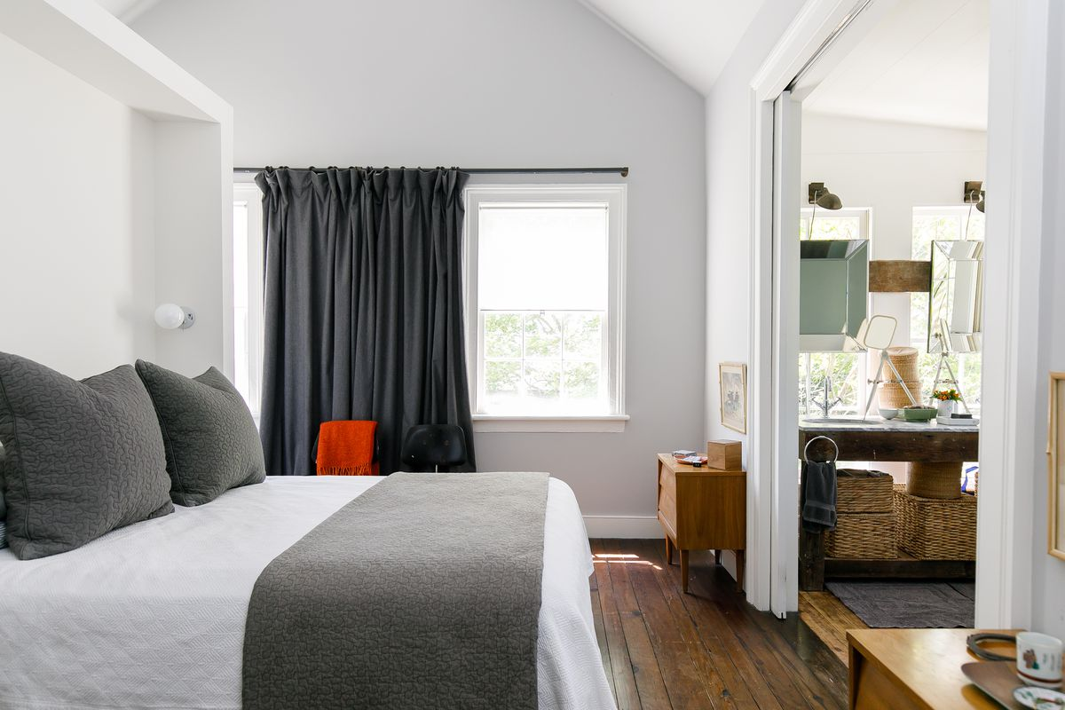 A bedroom with a bed with white and grey bedding and a window with dark grey drapes. The bed faces a doorway looking into a bathroom.