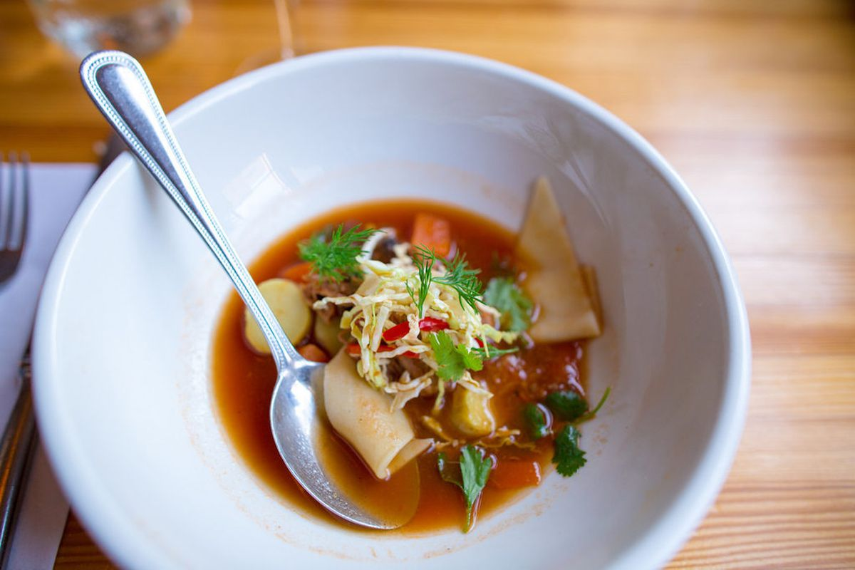 """Lamb neck lagman soup with tomato, fingerling potatoes, pickled red pepper, cabbage, egg noodles, and cilantro by Scott Garfinkel from the Momofuku Noodle Bar reunion at Brooklyn Star by <a href=""""http://www.flickr.com/photos/jmoranmoya/8624173048/in"""