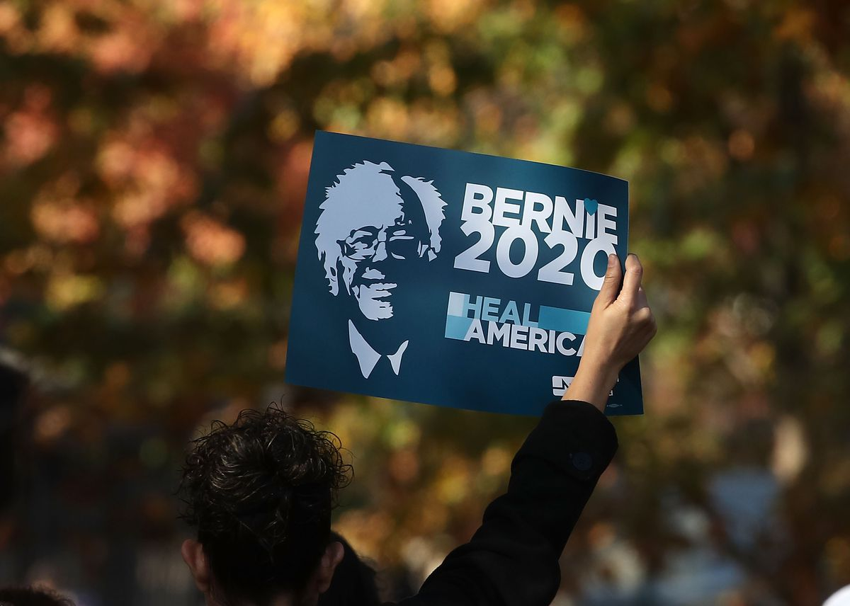 A protester holds a Bernie Sanders 2020 sign.