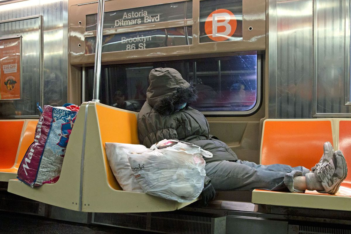 A person sleeps on a B train during a weekday.