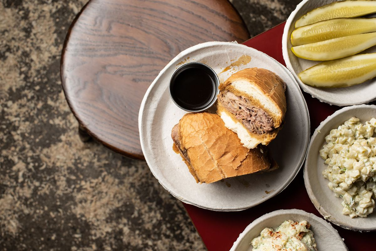 Philippe's French dip sandwich on a table surrounded by other accoutrement like pickles.