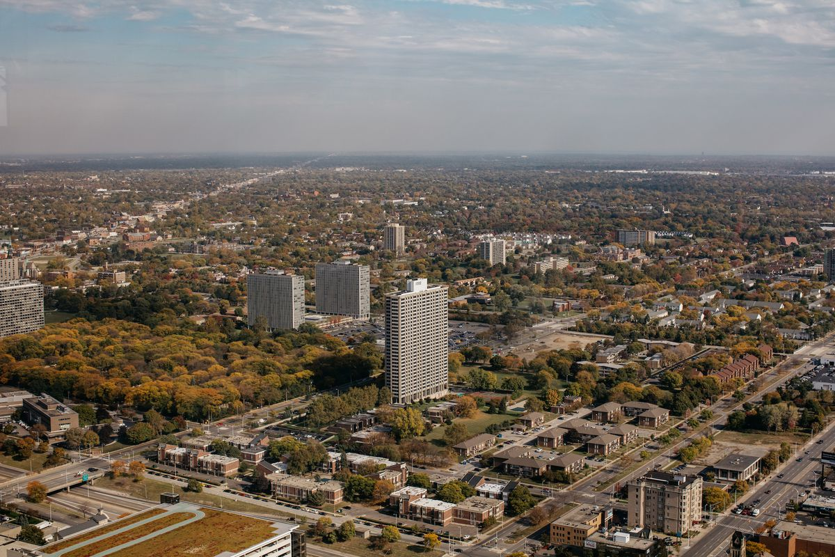 Aerial view of Lafayette Park. There are a couple of narrow towers, plus a number of smaller buildings and a park filled with trees.