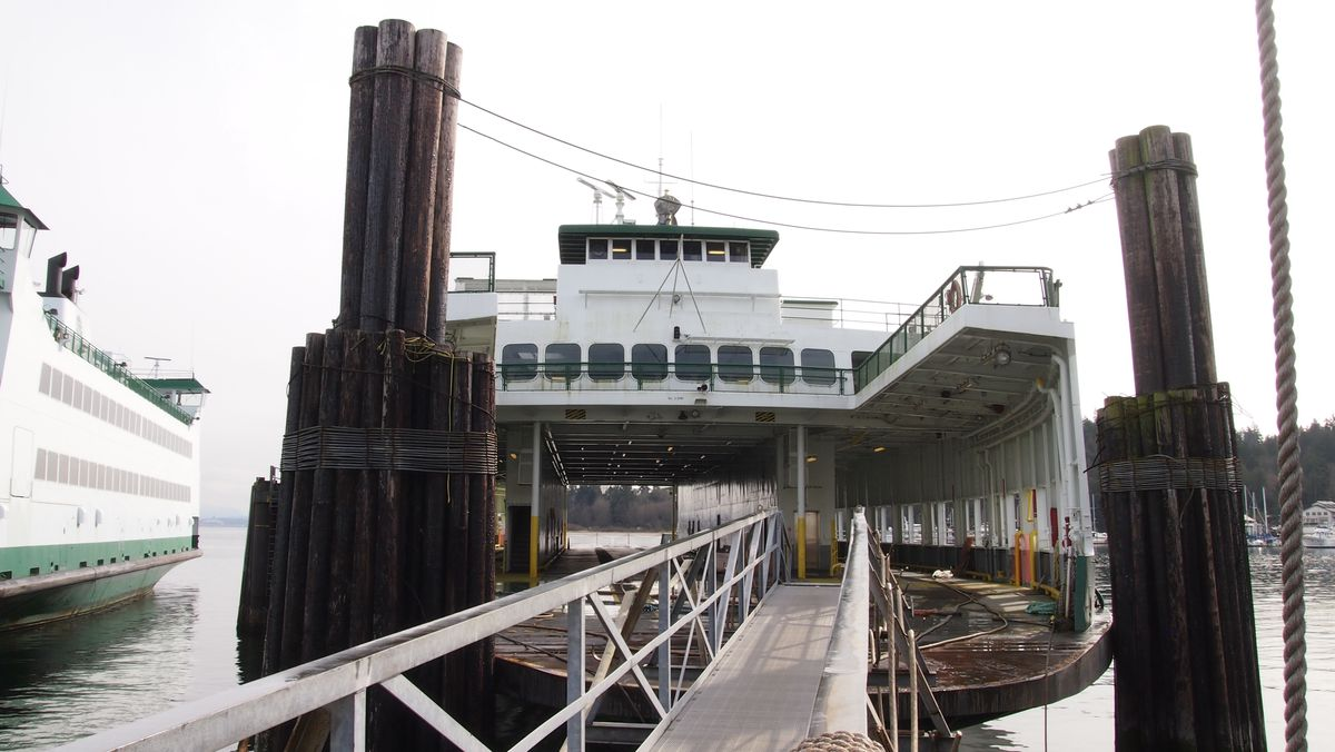 A metal gangway leads onto the car deck of a passenger ferry