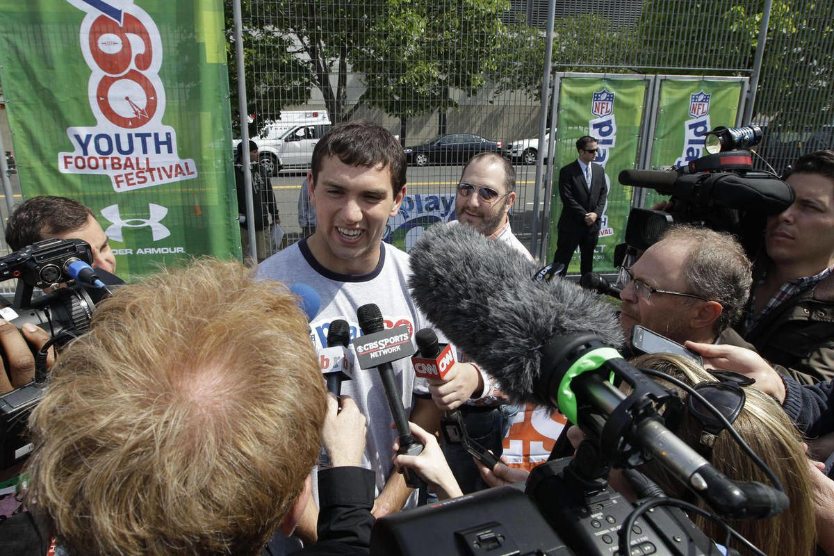 Andrew Luck is surrounded by reporters during the NFL Play 60 Youth Football Festival, Wednesday, April 25, 2012, in New York.