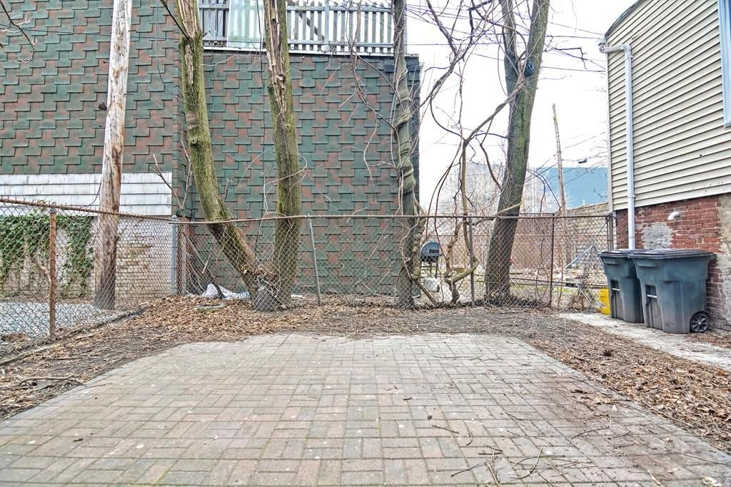 An empty brick patio with a fence around it and two garage bins off to the side.