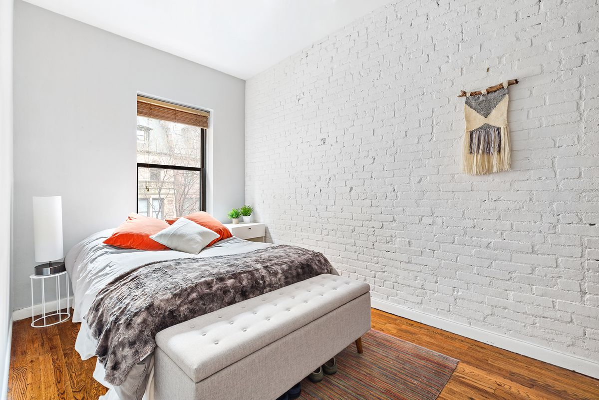 A bedroom with a large bed, exposed brick, hardwood floors, and one window.