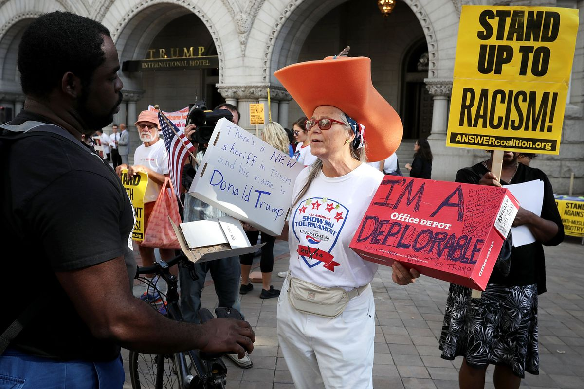 A supporter of Republican presidential candidate Donald Trump argues with protesters during a demonstration in front of the newly opened Trump International Hotel on September 12, 2016, in Washington, DC.