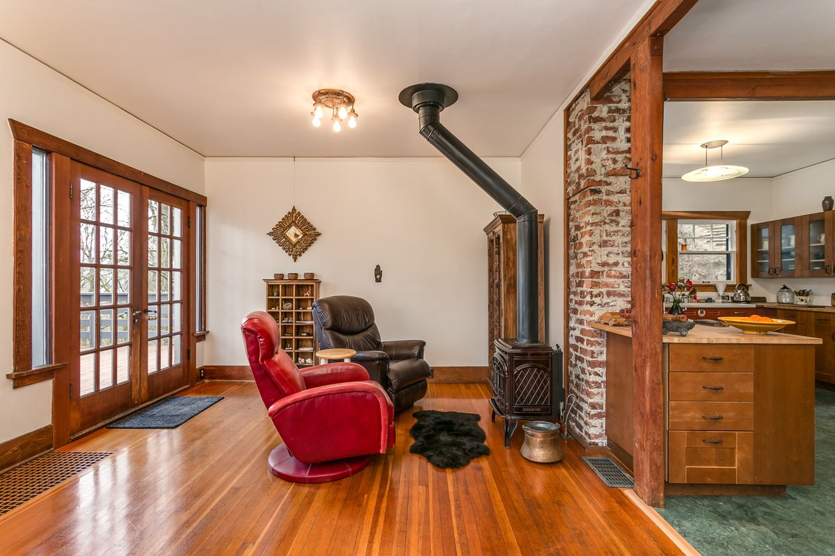A hardwood-floored living area with a cast iron stove. A brick accent wall and a wood-framed passageway lead to a kitchen with green tile floors.