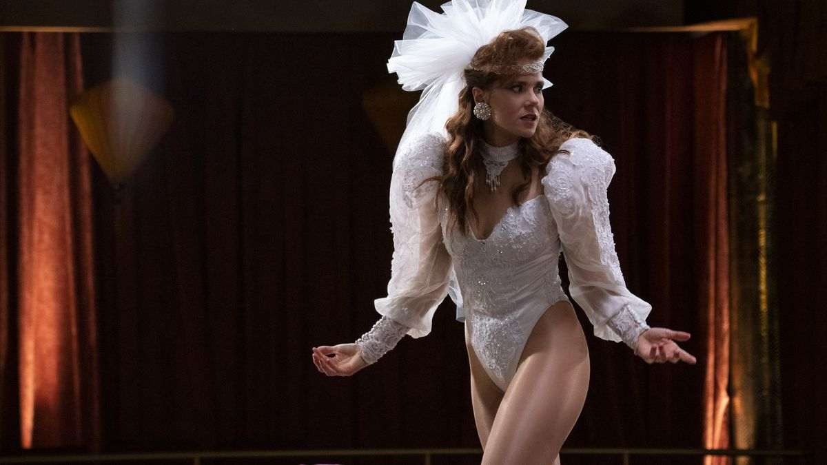 "Debbie (Betty Gilpin) stands on a lit stage wearing a unitard reminiscent of a wedding dress. Her palms are facing towards the sky as the extends her arms — it's kind of a ""come at me"" gesture. Her hair is perfectly curled and she's wearing a veil."