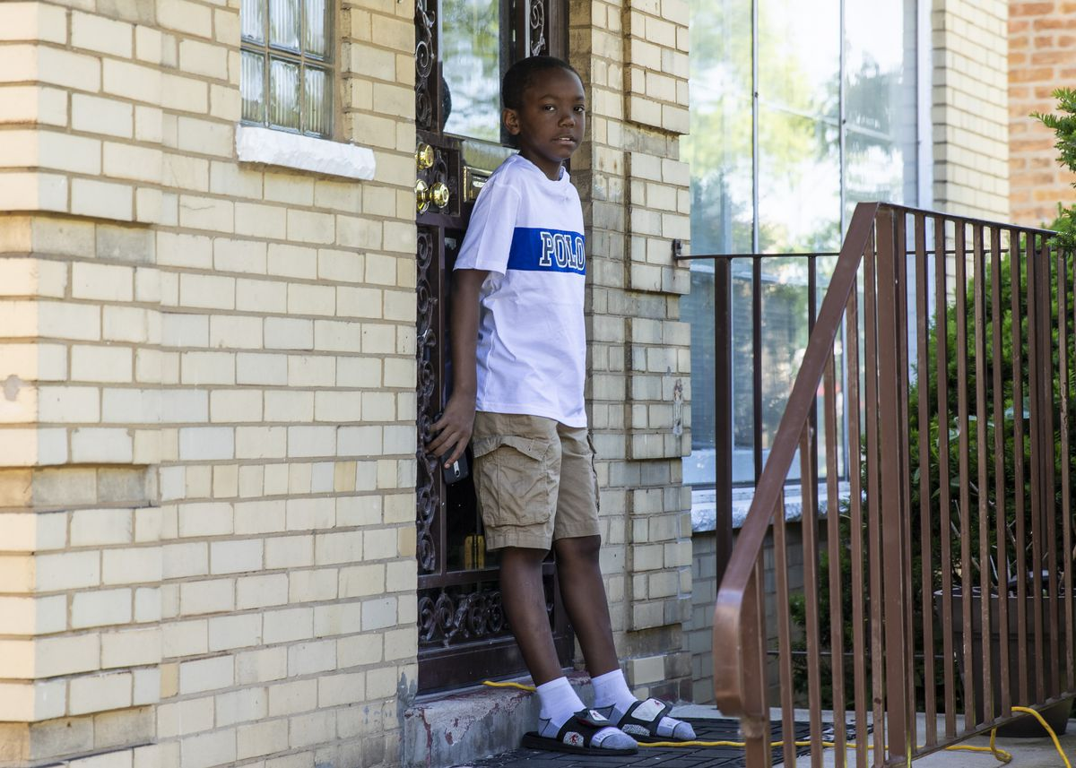 Zion Wilkins, 10, listens as his mom talks during a news conference outside their South Chicago Home.
