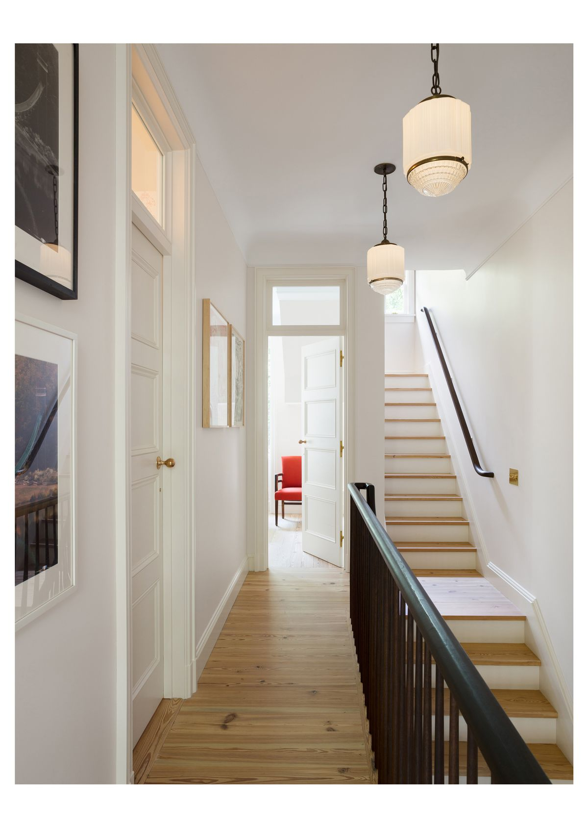 A hallway with a hardwood floor and white walls. There is a staircase with a black bannister and wooden stairs. There are hanging light fixtures. At the end of the hallway is a doorway where the door is open. There is a red chair in the room with the open