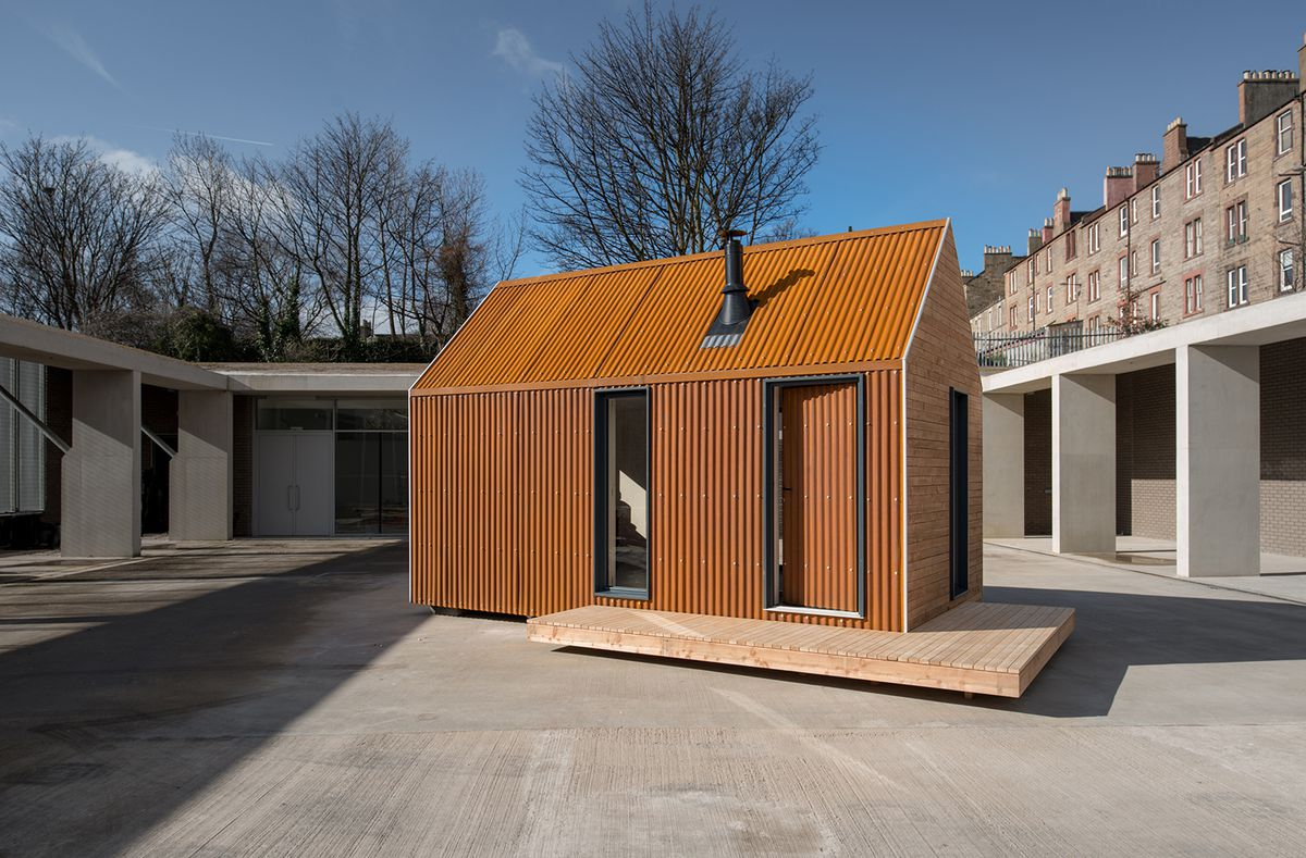 Small house with corrugated metal exterior in a city plaza.