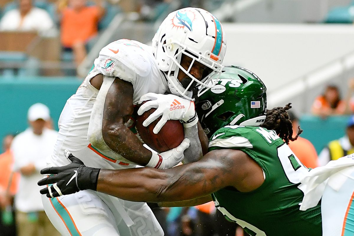 New York Jets nose tackle Steve McLendon brings down Miami Dolphins running back Kalen Ballage during the first half at Hard Rock Stadium.
