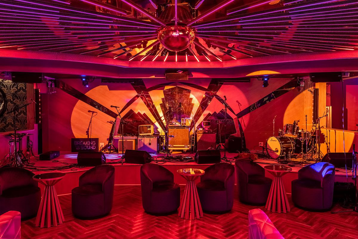 Supper club-style seating with stage, drums, and musical equipment.