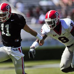 Aaron Murray, left, scrambles past Alec Ogletree during the first half of G-Day, the University of Georgia NCAA college spring football game in Athens, Ga., Saturday, April 14, 2012.