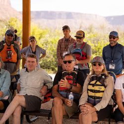 Susan Daggett, left, her husband, Sen. Michael Bennet, D-Colo., second from left, Sen. Mitt Romney, R-Utah, center, his wife Ann, second from right, and Utah Lt. Gov. Deidre Henderson, right, listen to a presentation during a rafting trip on the Colorado River northeast of Moab on Saturday, Sept. 18, 2021.