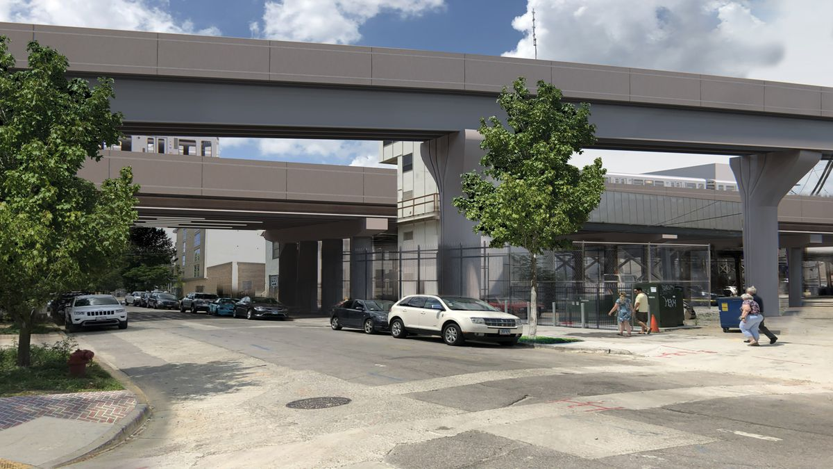 """A rendering shows the street view of the new grey CTA bypass. The elevated tracks are grey with concrete supports in a """"Y"""" shape with metal fencing surrounding facilities at the base."""