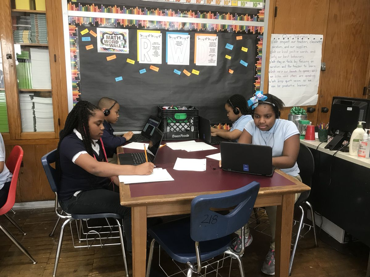 Students in a fifth-grade classroom use their laptops to conduct research for a Black History Month project.