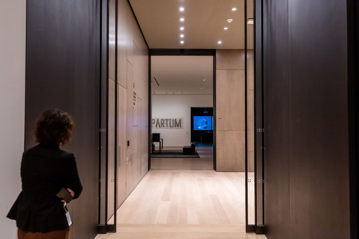A woman walks into a doorway with a view of an entrance into another gallery.
