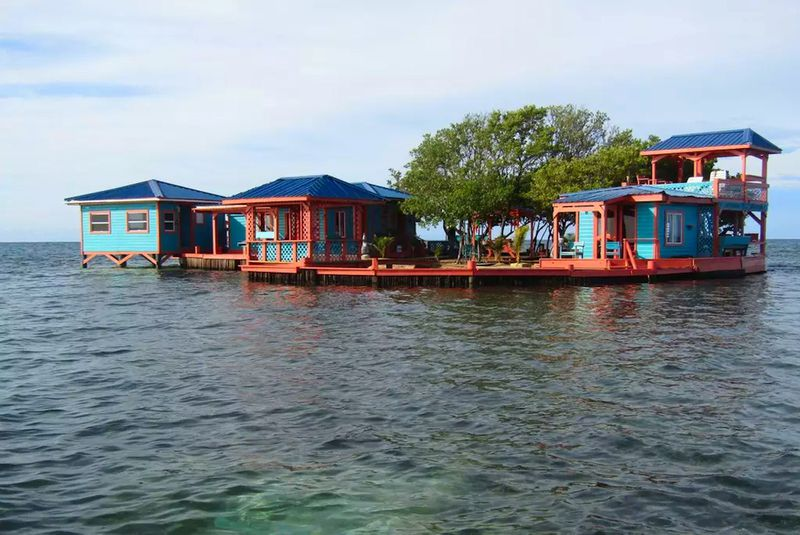 A floating collection of three teal houses with red trim and docks sits on water in Belize.