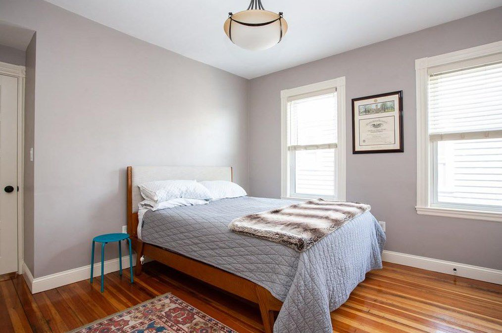 A bedroom with a bed, two windows, and a nightstand.