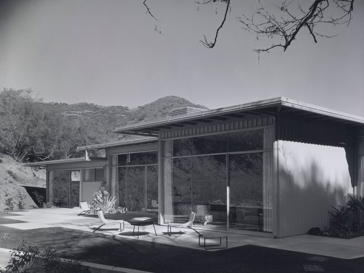 A house. There is a flat roof and large windows. There is an outdoor seating area outside of the house. In the distance is a mountain range.