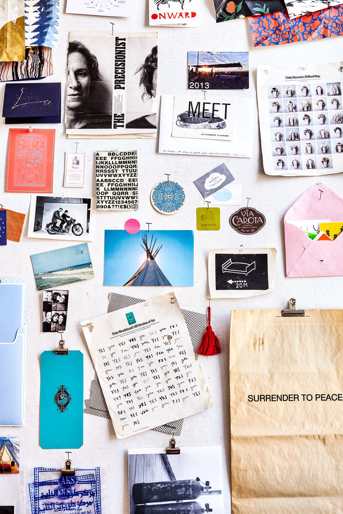 An inspiration board with multiple pieces of paper, photos, and magazine clippings.
